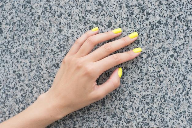 Professionelle nagelpflege. weibliche hand mit gelber nagelfarbe. auftragen von nagellack. maniküre im nagelstudio. acryl-overlays und -erweiterungen. kosmetische schönheitsbehandlung für fingernägel.