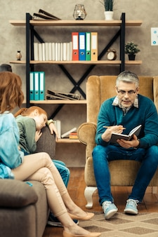 Professionelle psychologische hilfe. netter kluger mann, der mit seinen patienten spricht und ihnen professionelle psychologische hilfe gibt