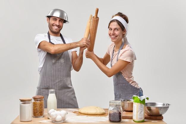Professionelle restaurantkonkurrenten kämpfen mit nudelhölzern, nehmen an kulinarischen kämpfen teil, schauen fröhlich zu, bereiten leckeres essen zu und bereiten sich auf das partywochenende vor. paar kocht zusammen