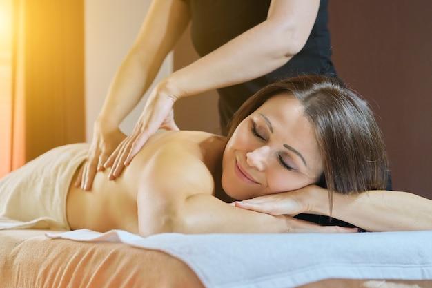 Professionelle rückenmassage, erwachsene frau, die auf massagetisch liegend behandelt wird