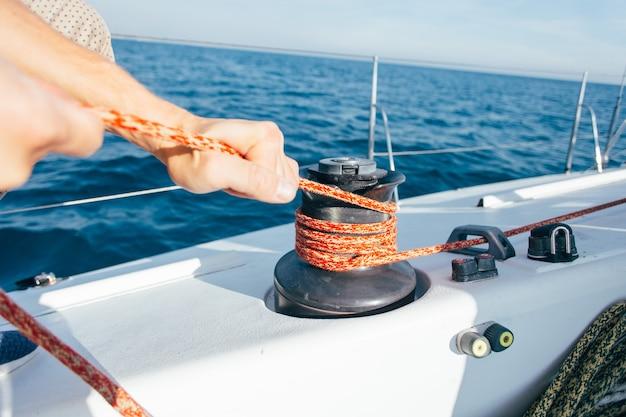 Professionelle segler- oder seglerstrumpfhose und spannseil oder drahtseil auf mechanischer winde auf segelboot oder yacht