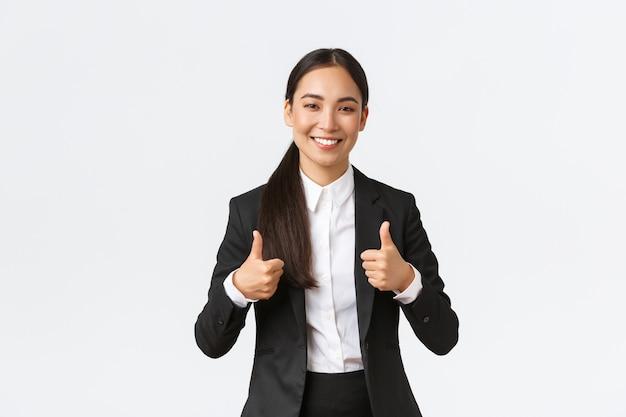 Professionelle selbstbewusste lächelnde asiatische geschäftsfrau versichert, dass alles gut läuft, daumen hoch zeigen, agentur oder produkt empfehlen, mögen und genehmigen, gut gemacht, gute arbeit oder gute arbeit sagen