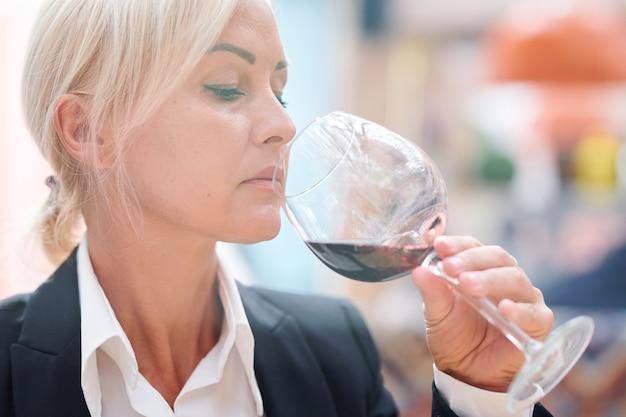 Professionelle sommelierin, die rotwein riecht, während sie ihren geschmack und ihre qualität bei der arbeit im restaurant überprüft