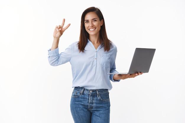 Professionelle sorglose, fröhliche kaukasierin der 30er jahre mit tattoo-arbeit, zuversichtlich, dass das projekt gut läuft, das friedenszeichen des sieges zeigen, den laptop halten, die weiße wand zufrieden stellen, die fertigstellung rechtzeitig versichern