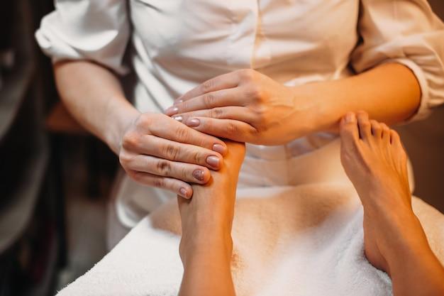 Professionelle spa-mitarbeiter massieren die füße des kunden während eines speziellen spa-eingriffs im salon