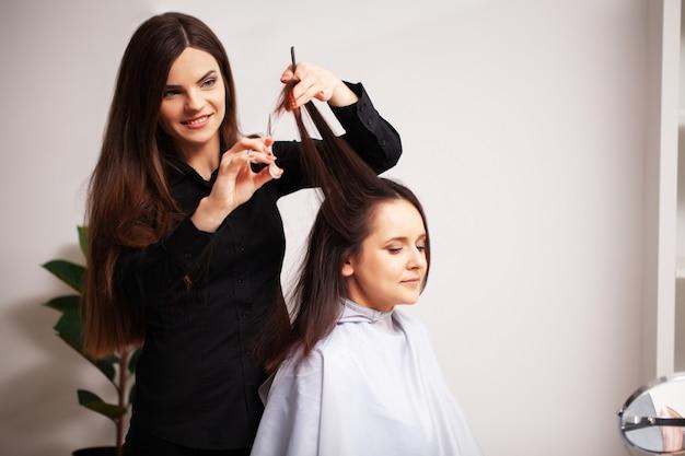 Professionelle stylistin macht eine junge frau zu einer schönen frisur.