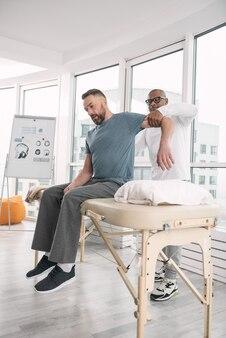 Professionelle therapie. kluger männlicher therapeut, der hinter seinem patienten steht, während er seinen arm hält