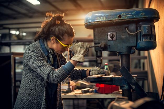 Professionelle tischlerin, die mit einer elektrischen bohrmaschine in der werkstatt arbeitet
