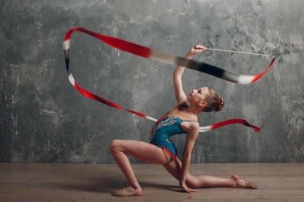 Professionelle turnerin des jungen mädchens tanzen rhythmische gymnastik mit band im studio.