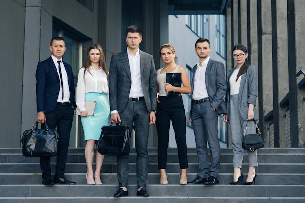 Professionelle unternehmensbüro business team mitglieder gruppe blick auf die kamera. sechs glückliche, stolze, selbstbewusste führungskräfte, mitarbeiter, mitarbeiter, menschengruppen stehen zusammen.