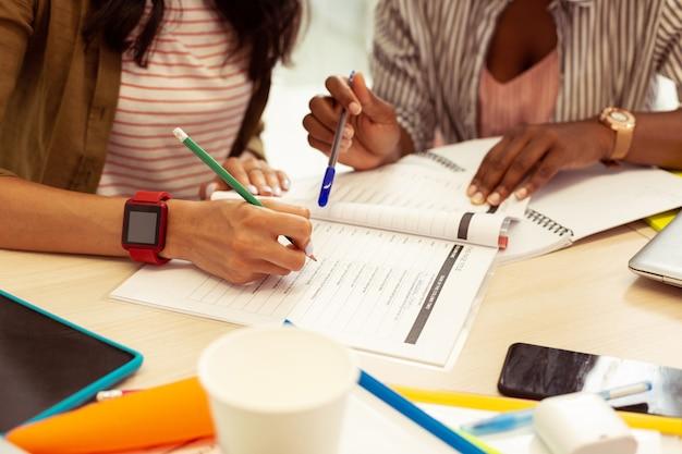 Professionelle unterstützung. aufmerksame langhaarige brünette sitzt am tisch und erledigt die aufgabe