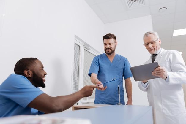Professionelle untersuchung genießen. kompetente, fröhliche, fleißige ärzte, die im krankenhaus arbeiten und in der nähe des krankenschwesterbüros stehen, meinungen austauschen und geräte verwenden