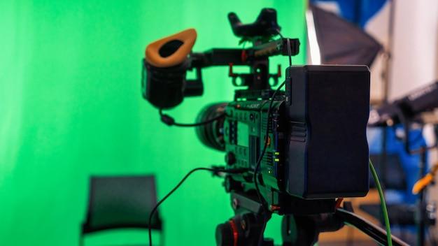Professionelle videokamera auf einem stativ mit grünem chromakey in einem studio