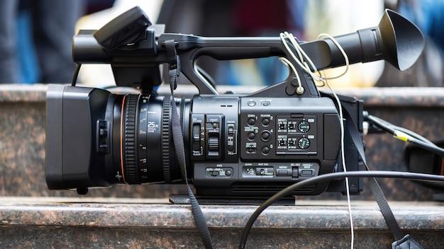 Professionelle videokamera mit kabeln auf steintreppen