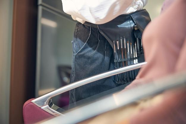 Professionelle visagistin, die in der nähe ihres kunden steht und sterile instrumente benutzt, während sie romantisches make-up macht doing