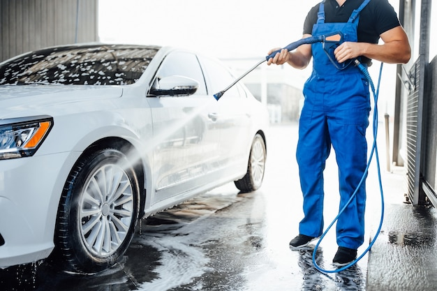Professionelle waschmaschine in blauer uniform, die luxusauto mit wasserpistole auf einer open-air-autowaschanlage wäscht