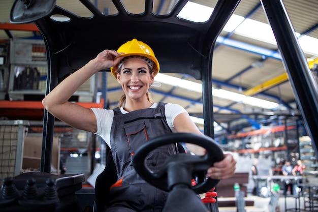 Professionelle weibliche industriefahrerin, die gabelstaplermaschine im fabriklager betreibt