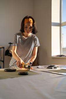 Professionelle weibliche kanalisation macht kleidungsmuster im studio mit elektrischem schneider auf dem tisch in der werkstatt