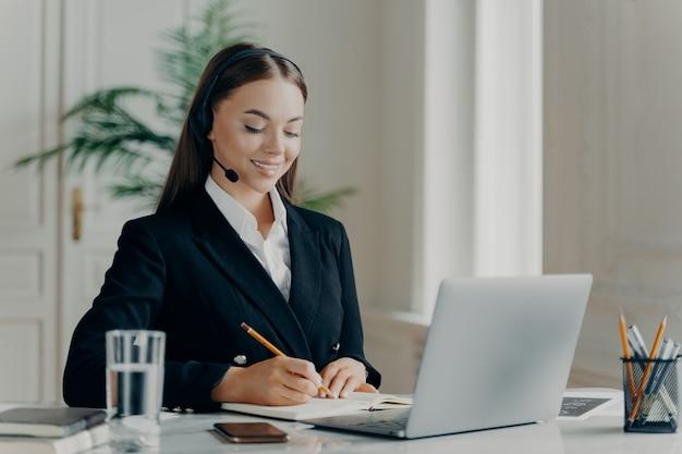 Professionelle weibliche unternehmensberaterin in formellem anzug und headset, die notizen macht und sich während der webkonferenz auf dem laptop zufrieden fühlt, managerin des callcenters, die vor dem laptop im büro sitzt