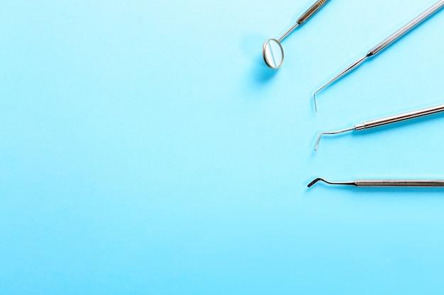 Professionelle zahnärztliche instrumente aus stahl mit einem spiegel auf hellblauem hintergrund mit freiem platz.