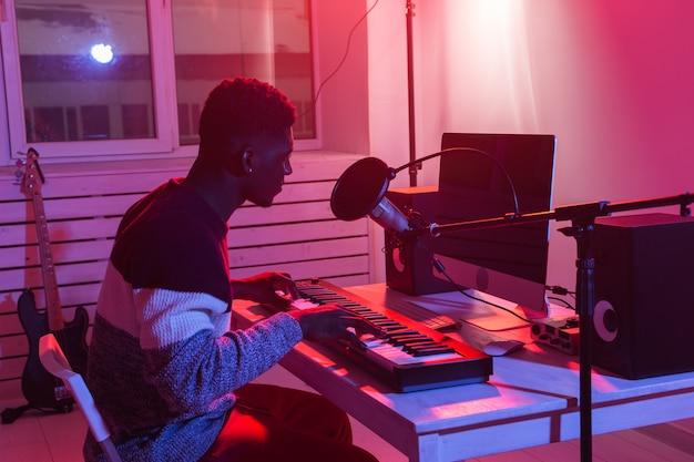 Professioneller afroamerikanischer musiker, der synthesizer im digitalen studio zu hause aufnimmt, musik