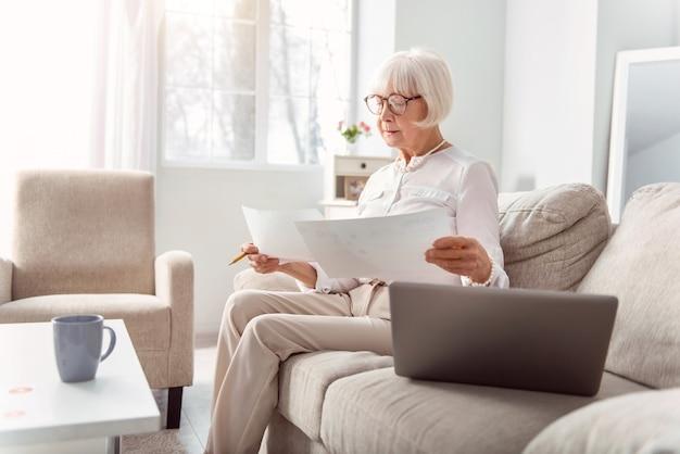 Professioneller analyst. zierliche ältere frau in einem noblen outfit, die auf der couch sitzt und die diagramme auf ausdrucken vergleicht, die umfragedaten analysiert