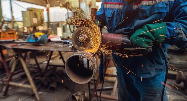 Professioneller arbeiter in schützendem, gleichmäßig schneidendem metallrohr mit elektrischem schleifer in der industriewerkstatt.
