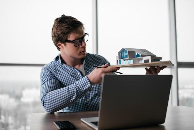 Professioneller architekt, der modell des hauses hält