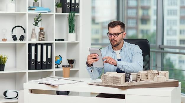 Professioneller architekt im büro inspiziert das projekt eines wohnkomplexes und macht