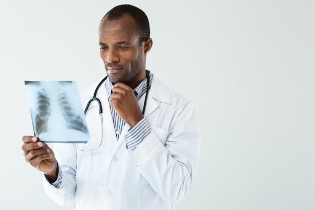 Professioneller arzt, der das ergebnis der radiologie während des holdign-röntgenscans analysiert
