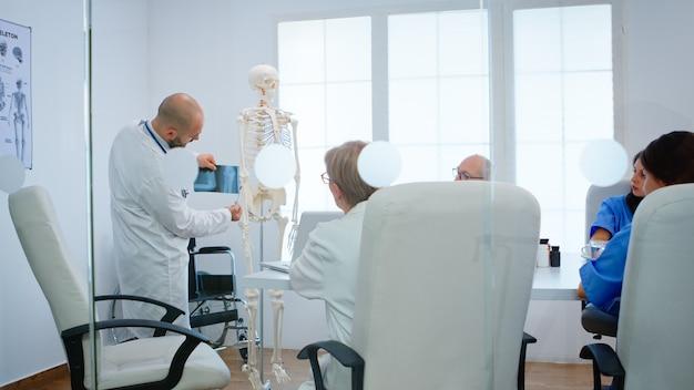 Professioneller arzt, der die körperknochenfunktionen von kollegen unter verwendung von radiographie und anatomischem modell des menschlichen skeletts lernt, das im krankenhausbüro steht. ärzte diskutieren über krankheitssymptome