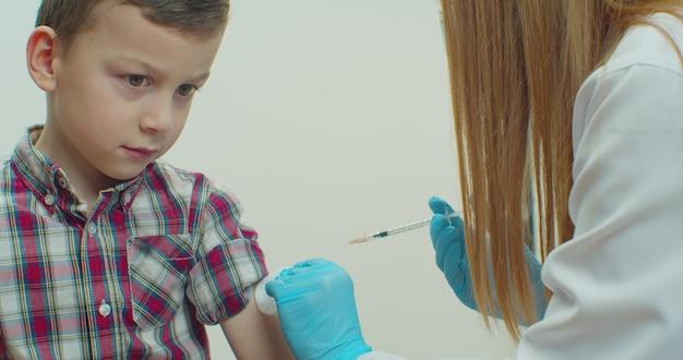 Professioneller arzt, der injektion zu kaukasischem kleinen jungenpatienten in maske zu hause während der coronavirus-pandemie macht