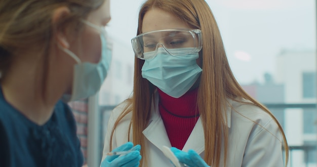 Professioneller arzt, der während der coronavirus-pandemie eine injektion an eine kaukasische kinderpatientin in einer maske zu hause macht.