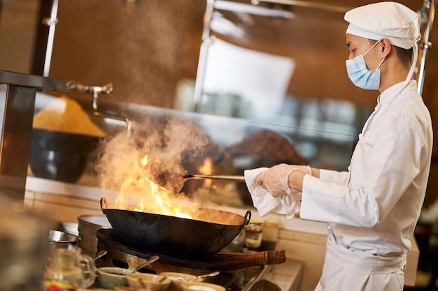 Professioneller asiatischer koch, der pfannengerichte im flammenden wok herstellt