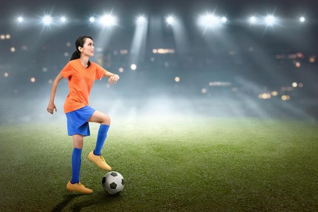 Professioneller asiatischer weiblicher fußballspieler in der aktion