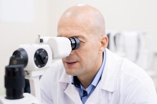 Professioneller augenarzt, der am arbeitsplatz durch medizinische geräte schaut und dabei das sehvermögen des patienten bei der arbeit überprüft