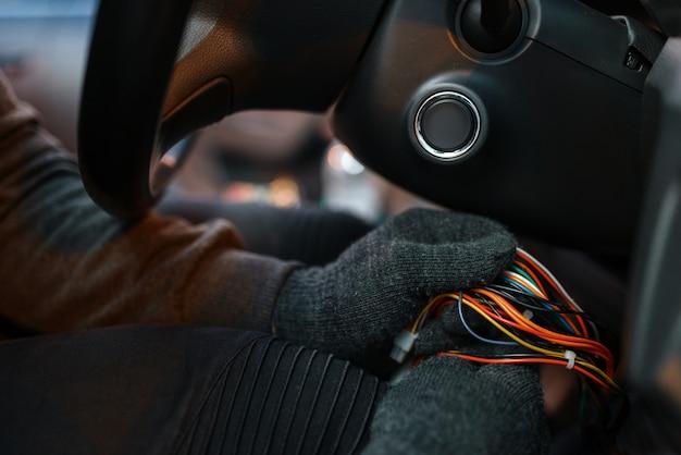 Professioneller autodieb, der zündschloss hackt, krimineller lebensstil.