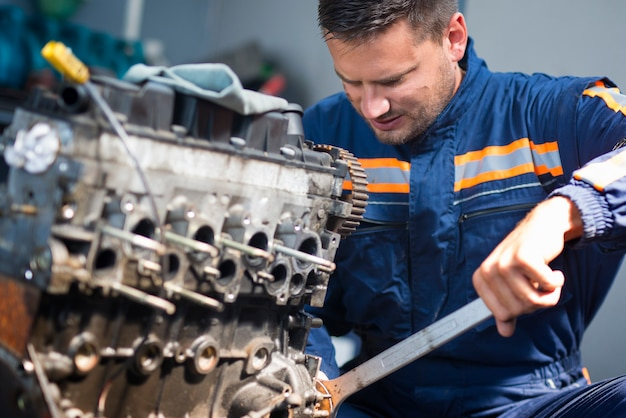 Professioneller automechaniker, der den automotor mit einem schraubenschlüssel in der werkstatt repariert