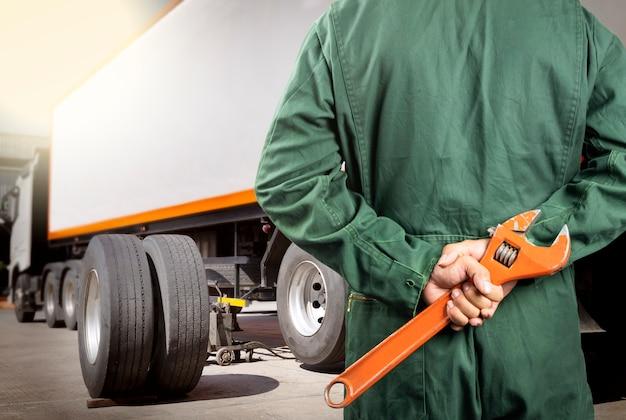 Professioneller automechaniker, der großen schlüssel für wartung die lkw-räder hält.