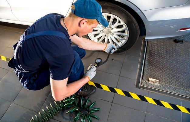 Professioneller automechaniker, der im autoreparaturservice arbeitet. reparatur von rädern.