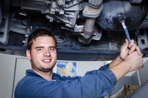 Professioneller automechaniker in der werkstatt, die das auto repariert