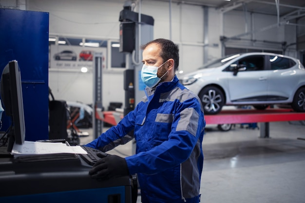Professioneller automechaniker mit gesichtsschutzmaske, der in der fahrzeugwerkstatt während der koronavirus-pandemie arbeitet.