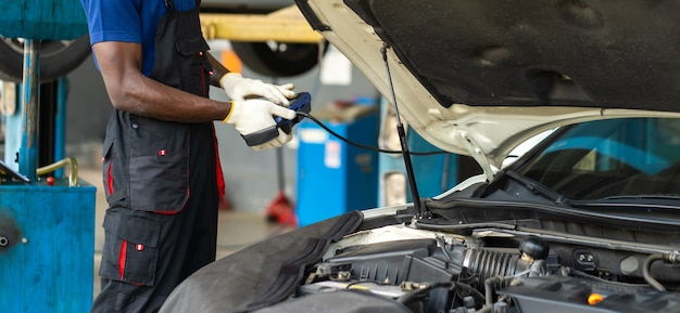 Professioneller automechaniker-reparaturservice und überprüfung des automotors durch diagnosesoftware-computer. sachkundiger mechaniker, der in einer autowerkstatt arbeitet.