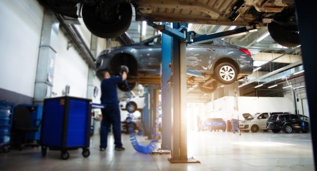 Professioneller automechaniker repariert ein auto an einer tankstelle und verwendet spezialwerkzeuge