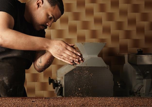Professioneller bäcker gießt körnige nüsse auf eine form, die mit geschmolzener schokoladenmasse gefüllt ist. zubereitung von leckerem kuchen aus bio-schokolade in handwerklichen süßwaren zum verkauf