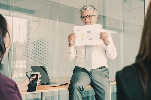 Professioneller bärtiger ceo, der auf tisch sitzt und grafik zeigt
