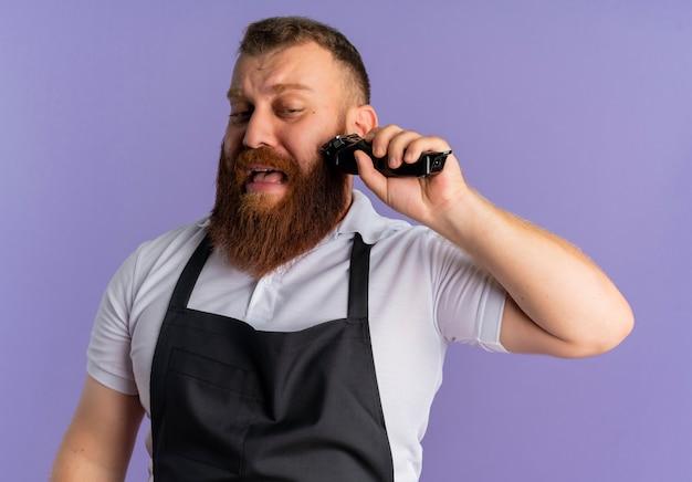 Professioneller bärtiger friseurmann in der schürze, der seinen bart mit rasiermaschine schneidet, verwirrt mit traurigem ausdruck auf gesicht, das über lila wand steht