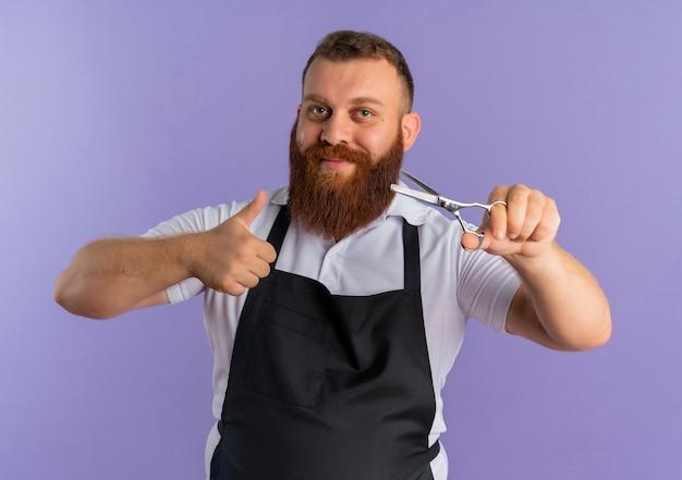 Professioneller bärtiger friseurmann in der schürze, die eine lächelnde schere hält, die fröhlich zeigt daumen hoch über lila wand