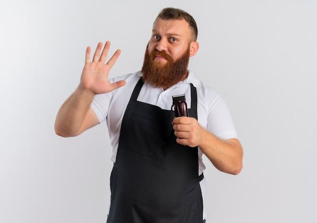 Professioneller bärtiger friseurmann in der schürze, die haarschneidemaschine hält, die mit der hand verwirrt über weißer wand steht