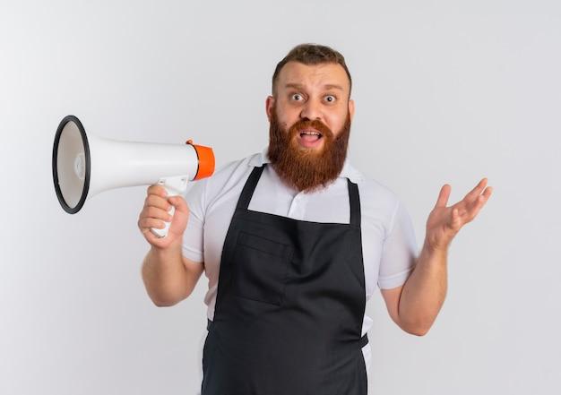Professioneller bärtiger friseurmann in der schürze, die megaphon hält, das verwirrte ausbreitende arme zur seite steht, die über weißer wand stehen